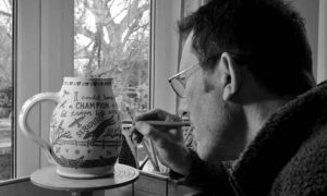 Simon Olley working on sgraffito jug after throwing on the pottery wheel, making perfect gifts for dog lovers – Studio Pottery by Simon Olley